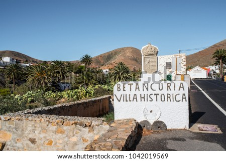 01-29-2018 Betancuria, Fuerteventura, Spain: historic town sign in Betancuria with village and mountain range in background against blue sky #1042019569