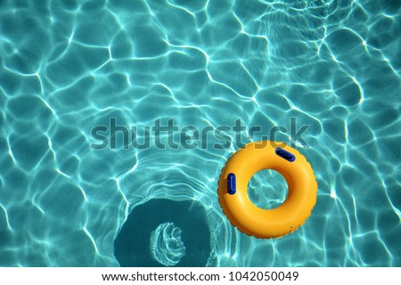 Yellow pool ring floating in a refreshing cool blue swimming pool. #1042050049