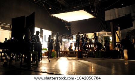 Behind the scenes or the making of film video production and movie crew team working in silhouette of camera and equipment set in studio.  Royalty-Free Stock Photo #1042050784
