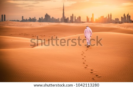 Arabic man with traditional emirates clothes walking in the desert Royalty-Free Stock Photo #1042113280