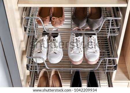 Different shoes on shelves of wardrobe closet Royalty-Free Stock Photo #1042209934
