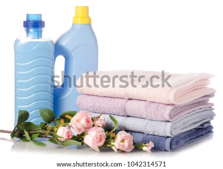 A stack of towels flower softener conditioner liquid laundry detergent on white background isolation #1042314571