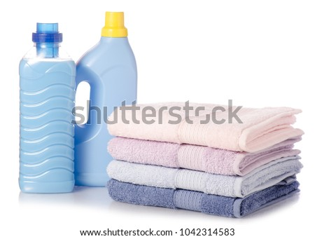 A stack of towels softener conditioner liquid laundry detergent on white background isolation #1042314583