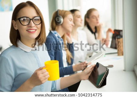 Young happy beautiful short haired businesswoman smiling to the camera joyfully holding cup of coffee relaxing at her workplace copyspace her colleagues working on the background. #1042314775