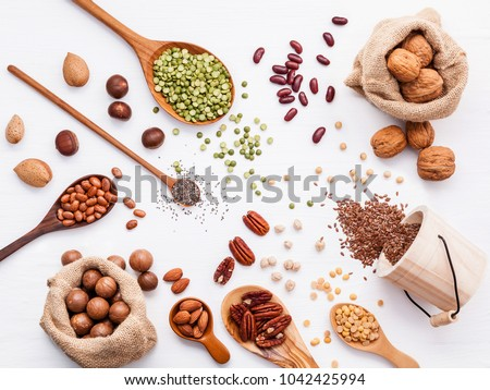 Various legumes and different kinds of nuts walnuts kernels ,hazelnuts, almond kernels,brown pinto ,soy beans ,flax seeds ,chia ,red kidney beans and pecan set up on white wooden table. #1042425994