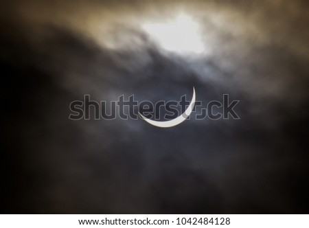 a sharp eclipse through clouds in England #1042484128