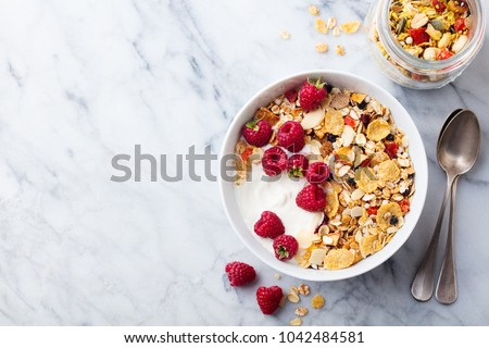 Healthy breakfast. Fresh granola, muesli with yogurt and berries on marble background. Top view. Copy space. #1042484581