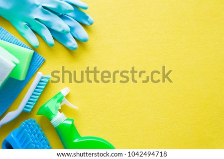 Colorful cleaning set for different surfaces in kitchen, bathroom and other rooms. Empty place for text or logo on yellow background. Cleaning service concept. Early spring regular clean up. Top view. #1042494718