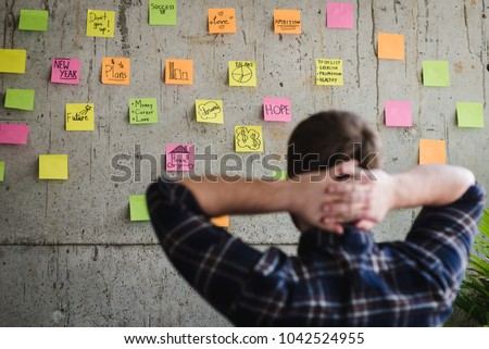 Back of entrepreneur sitting in office and look at colorful sticky message on cement wall. Work lifestyle concept.  Selective focus. Royalty-Free Stock Photo #1042524955
