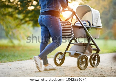 Woman with baby stroller walks in the park at sunset Royalty-Free Stock Photo #1042556074