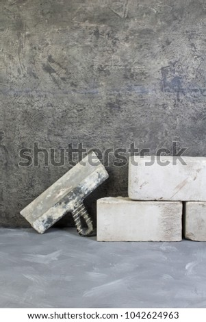 bricks, putty knife on the gray concrete background. Copy space. Top view #1042624963