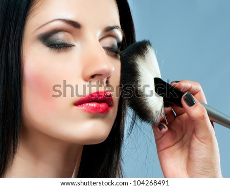 portrait of a beautiful young woman with make-up brush #104268491