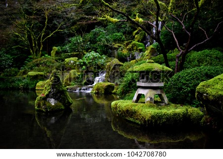 An image taken at the Portland Japanese Zen Garden. The image includes a waterfall flowing in the background with moss covered lantern standing in the foreground.