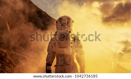 Courageous Astronaut in the Space Suit Explores Red Planet Mars Covered in Mist. Adventure. Space Travel, Habitable World and Colonization Concept. #1042736185
