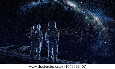 Crew of Two Astronauts in Space Suits Standing on the Moon Looking at the The Milky Way Galaxy. High Tech Concept of Moon Colonization and Space Travel. #1042736407