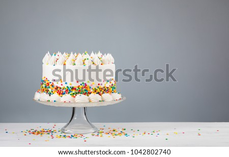 Vanilla buttercream Birthday cake with colorful sprinkles over a neutral background.