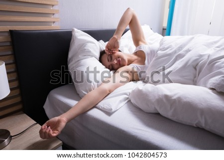 Smiling Young Woman Lying On Bed In Bedroom #1042804573