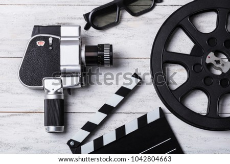 Elevated View Of Movie Camera, 3d Glasses, Film Reel And Clapper Board On Wooden Plank #1042804663