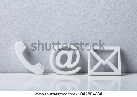 Contact Methods. Close-up Of A Phone, Email and Post Icons Leaning On White Wall #1042804684