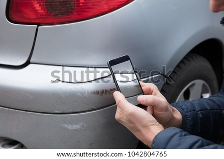 Close-up Of A Person's Hand Taking Photo Of Damaged Car Through Smartphone