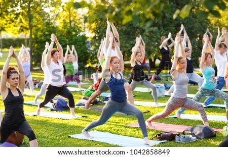big group of adults attending a yoga class outside in park #1042858849