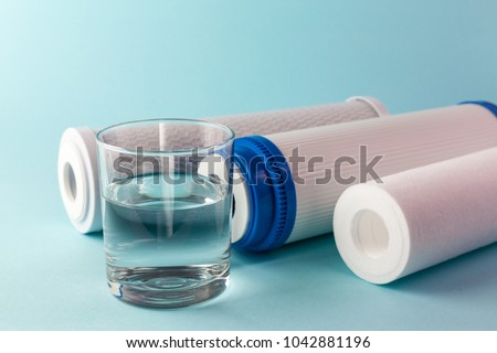 A glass of water on the background of filter cartridges #1042881196