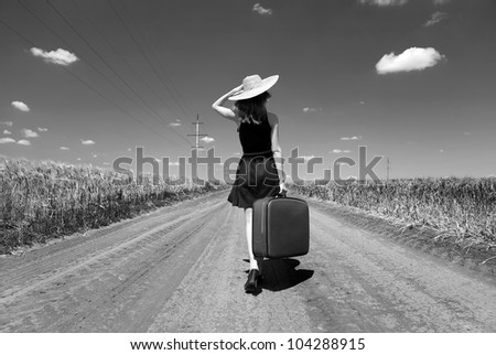 Lonely girl with suitcase at country road. Photo in black and white color style. #104288915