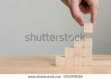 Hand arranging wood block stacking as step stair on wooden table. Business concept for growth success process. Copy space Royalty-Free Stock Photo #1042908586