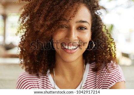 Close up shot of adorable African American woman has broad smile, wears striped t shirt, being in good mood, rests in cafeteria with best friends. Smiling dark skinned young female poses indoor #1042917214