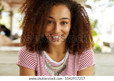Portrait of happy of dark skinned female with curly bushy Afro hairstyle, smiles broadly into camera, rests in cafe with boyfriennd, being glad to have much spare time. People, ethnicity concept #1042917217