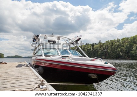 A wakeboard boat at a wooden dock in the Muskokas on a sunny day.  #1042941337