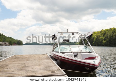 A wakeboard boat at a wooden dock in the Muskokas on a sunny day.  #1042941343