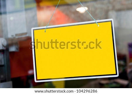 gorgeous yellow sign hanging on a window door outside a restaurant, store, office or other (copy-space available for design)