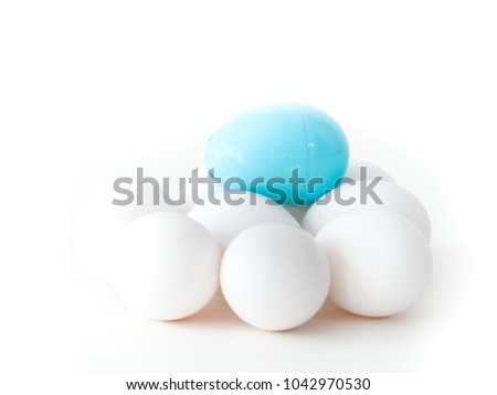 A close up photograph of a pile of real chicken eggs and a light blue plastic Easter egg on top isolated on a white background making a beautiful holiday wallpaper with white open space around image.