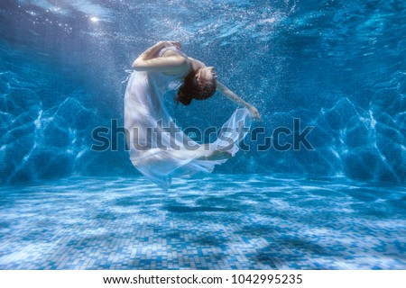 Girl shows the performance under the water, she dances in a white dress. #1042995235