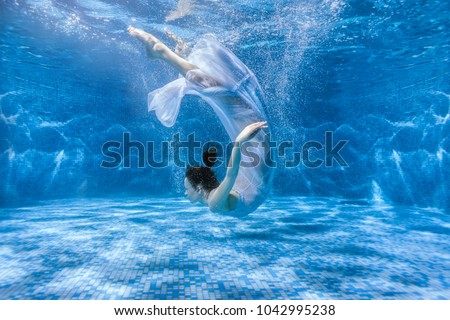 Woman dances under the water, she is in the pool. #1042995238