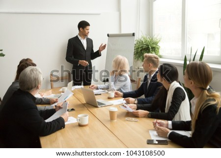 African businessman ceo boss in suit presenting corporate plan on flip chart at group meeting, black business coach leader giving presentation explaining team goals in conference room at training #1043108500