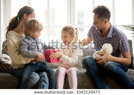 Sister presenting gift for little brother giving cute boy box with present, excited kid girl making surprise congratulating brother, happy family and children celebrating son birthday at home concept #1043120473