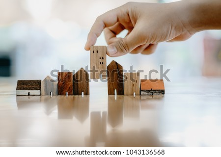 Hand choosing mini wood house model from model and row of coin money on wood table, selective focus, Planning to buy property. Choose what's the best. A symbol for construction ,ecology, loan concepts #1043136568