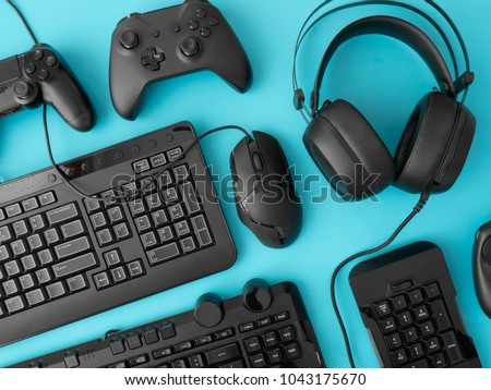 gamer workspace concept, top view a gaming gear, mouse, keyboard, joystick, headset on blue table background.