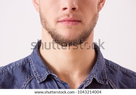 Close up of young unshaved man isolated over white background. Portrait of bearded hipster man's face in denim shirt standing against white background. Man expressing his masculinity and charisma #1043214004