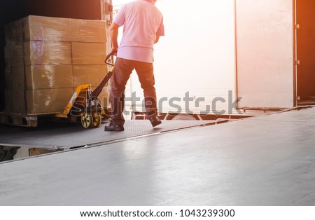 Worker man dragging hand pallet truck or manual forklift with the shipment pallet unloading from a truck. #1043239300