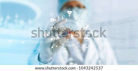 Medicine doctor holding a color capsule pill in hand with icon medical network connection on modern virtual screen interface in laboratory background, medical technology network concept #1043242537