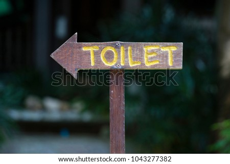 A vertical view of classic simple design handmade wooden sign of toilet give direction to WC , Thailand. Close up