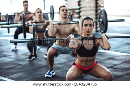 Group of sporty muscular people are working out in gym. Cross fit training. Handsome shirtless men and attractive women are doing exercises with barbells. Weightlifting. #1043284735