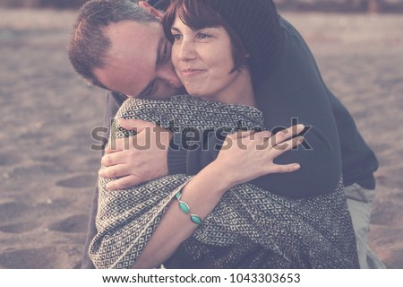 cute man and woman middle aged having fun in love at the beach outdoor. leisure activity and big hug for love concept and romantic scene the man embrace her. sand on the background