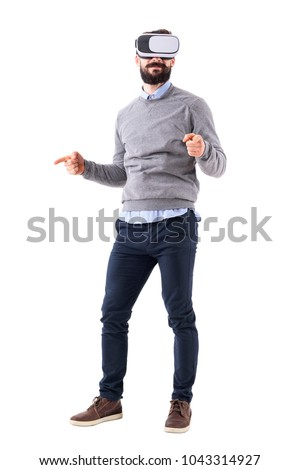 Happy excited adult man wearing vr glasses pointing finger resizing gesture. Full body isolated on white background.