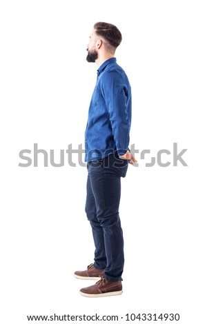 Side view of young stylish bearded man with hands in back pockets standing and watching. Full body isolated on white background. #1043314930