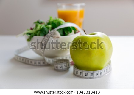 Measuring tape around the apple, bowl of green salad and glass of juice. Weight loss and right nutrition concept #1043318413