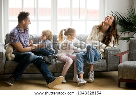 Happy parents and kids having fun tickling sitting together on sofa, cheerful couple laughing playing game with little active children son and daughter in living room at home, family funny activity #1043328154
